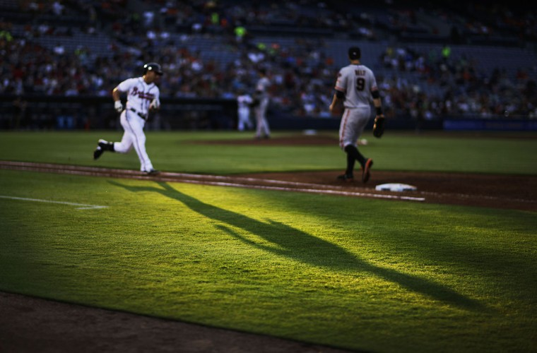 Atlanta Braves' Daniel Castro casts a shadow on the field as he runs to first base after hitting a single during the third inning of a baseball game against the San Francisco Giants Tuesday, Aug. 4, 2015, in Atlanta. (AP Photo/David Goldman)