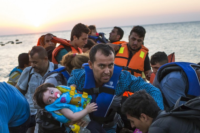 A man carries a girl in his arm as migrants arrive at a coast on a dinghy after crossing from Turkey in the southeastern island of Kos, Greece, during the sunrise early Thursday, Aug. 13, 2015. Greece has become the main gateway to Europe for tens of thousands of refugees and economic migrants, mainly Syrians fleeing war, as fighting in Libya has made the alternative route from north Africa to Italy increasingly dangerous. (AP Photo/Alexander Zemlianichenko)
