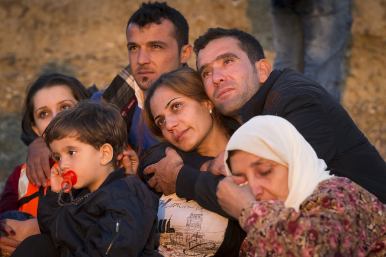Migrants family members hug each other after successfully arriving at a coast on a dinghy after crossing from Turkey, in the southeastern island of Kos, Greece, early Thursday, Aug. 13, 2015. Greece has become the main gateway to Europe for tens of thousands of refugees and economic migrants, mainly Syrians fleeing war, as fighting in Libya has made the alternative route from north Africa to Italy increasingly dangerous. (AP Photo/Alexander Zemlianichenko)