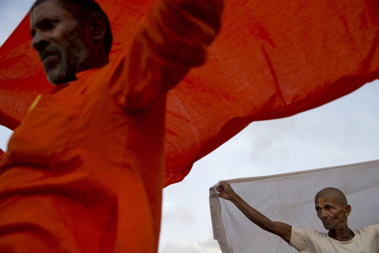 Hindu holy men dry their clothes after bathing in the Godavari River during Kumbh Mela, or Pitcher Festival, in Nasik, India, Wednesday, Aug. 26, 2015. Hindus believe taking a dip in the waters of the holy river during the Kumbh Mela will cleanse them of their sins. (AP Photo/Tsering Topgyal)