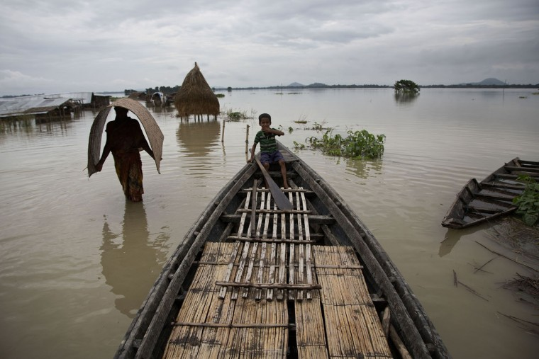Indian villagers affected by monsoon rains move through a flooded area in Morisuti village, about 65 kilometers (40 miles) east of Gauhati, India, Sunday, Aug. 23, 2015. The flooding in India's northeastern Assam state is the worst in the past three years, affecting nearly 600,000 people in 19 of the state's 27 districts, officials said. (AP Photo/Anupam Nath)