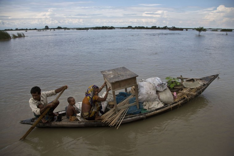 An Indian family sail through a flood-affected area in Xandohkhaitee village, about 80 kilometers (50 miles) east of Gauhati, India , Saturday, Aug. 22, 2015. State authorities say that monsoon flooding has nearly 200,000 people to leave their homes and take shelter in state-run tents this week. The area is prone to flooding during the June-to-September monsoon season. (AP Photo/Anupam Nath)