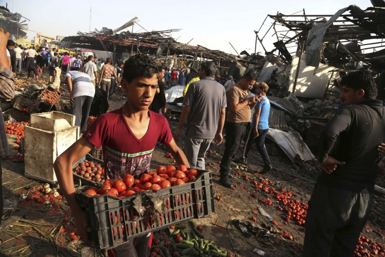 An Iraqi boy working for a grocery store collects his vegetables after a truck bomb attack in Jameela market in the predominantly Shiite neighborhood of Sadr City, Baghdad, Iraq, Thursday, Aug. 13, 2015. The massive truck bomb ripped through the popular Baghdad food market in the Iraqi capital's crowded neighborhood in the early morning hours on Thursday, killing tens of people, police officials said, in one of the deadliest single blasts in the capital in years. (AP Photo/Karim Kadim)