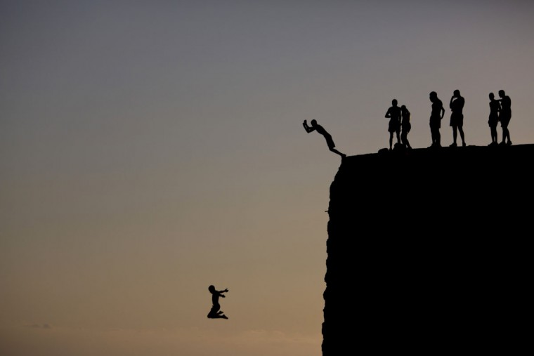 Israeli Arab boys jump into the Mediterranean sea from the ancient wall surrounding the old city of Acre, northern Israel, Monday, Aug. 31, 2015. (AP Photo/Ariel Schalit)