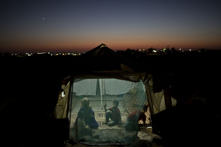 In this Wednesday, July 22, 2015 photo, Syrian refugee Eidah Hassoun, 36, sits with her children inside their tent at an informal tented settlement near the Syrian border on the outskirts of Mafraq, Jordan. More than 10,000 children have died in Syria's four-year conflict, while over 2.8 million in and out of the country donít go to school, according to the U.N. children's agency, UNICEF. (AP Photo/Muhammed Muheisen)