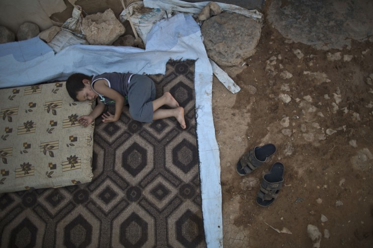A Syrian refugee child sleeps on the ground outside his family's tent to escape the heat trapped inside at an informal tented settlement near the Syrian border on the outskirts of Mafraq, Jordan, Wednesday, Aug. 19, 2015. (AP Photo/Muhammed Muheisen)