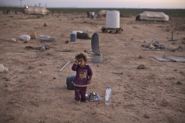 A Syrian refugee child drinks tea while standing outside her family's tent at an informal tented settlement near the Syrian border on the outskirts of Mafraq, Jordan, Wednesday, Aug. 26, 2015. (AP Photo/Muhammed Muheisen)