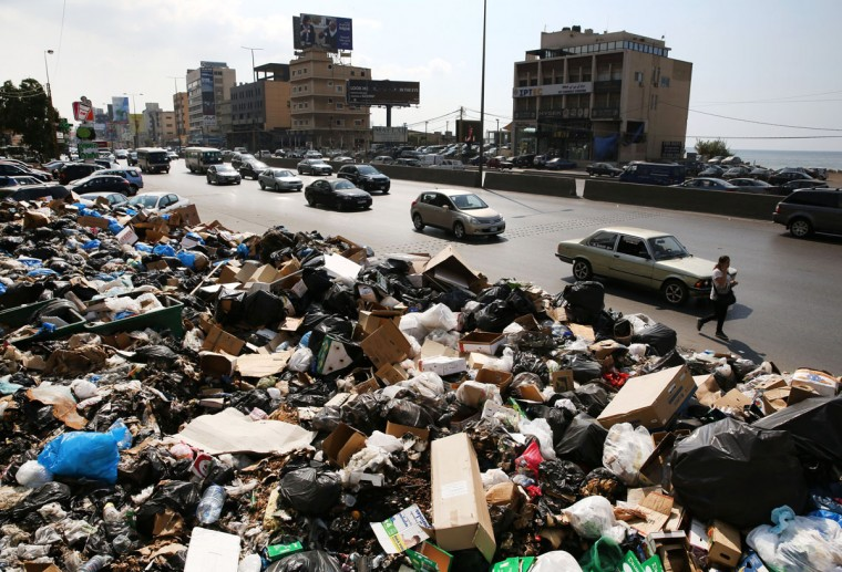 Lebanese citizens pass a pile of garbage blocking a street in the town of Jal el-Dib east Beirut, Lebanon, Wednesday, Aug. 26, 2015. Protests continued Wednesday over the country's worsening garbage collection crisis. (AP Photo/Bilal Hussein)