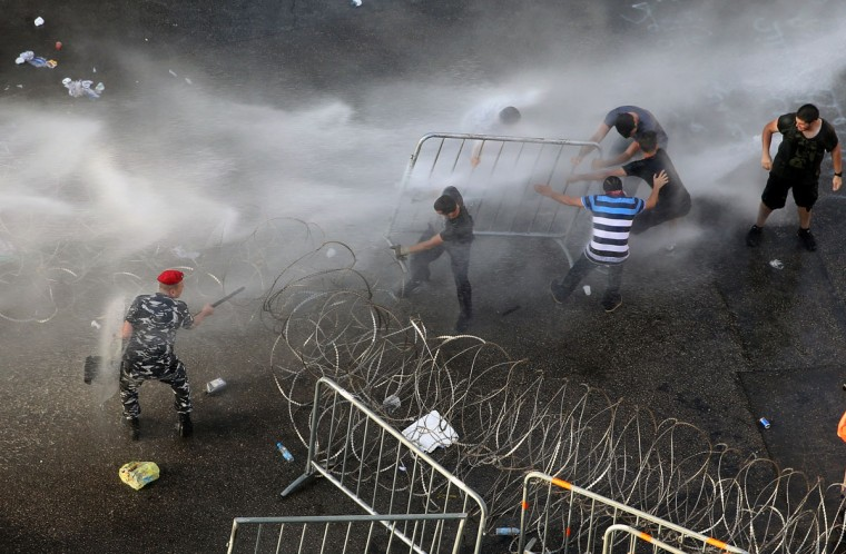 """Lebanese activists, right, remove barriers as they try to cross to the government house, as riot police spray them with water cannons during a protest against the ongoing trash crisis, in downtown Beirut, Lebanon, Wednesday, Aug. 19, 2015. Lebanon's health minister says the country is on the brink of a """"major health disaster"""" unless an immediate solution is found for its mounting trash problem. Garbage has been collecting on the streets in Lebanon for the past month amid government paralysis and inability to agree on a solution after Beirut's main landfill was closed down. (AP Photo/Hussein Malla)"""