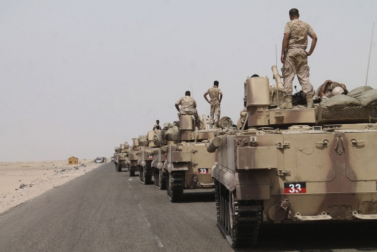 In this photo taken on Monday, Aug. 3, 2015, fighters against Shiite rebels known as Houthis stand on their armored vehicles on a road leading to Al-Anad base near Aden in the southern province of Lahej, Yemen. Pro-government troops seized the base from Shiite rebels on Monday, military officials said. The capture of Al-Anad was a significant victory for the forces allied to Yemen's exiled President Abed Rabbo Mansour Hadi in their battle to reverse the gains of Houthis. (AP Photo/Wael Qubady)