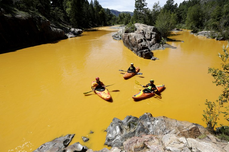 People kayak in the Animas River near Durango, Colo., Thursday, Aug. 6, 2015, in water colored from a mine waste spill. The U.S. Environmental Protection Agency said that a cleanup team was working with heavy equipment Wednesday to secure an entrance to the Gold King Mine. Workers instead released an estimated 1 million gallons of mine waste into Cement Creek, which flows into the Animas River. (Jerry McBride/The Durango Herald via AP)
