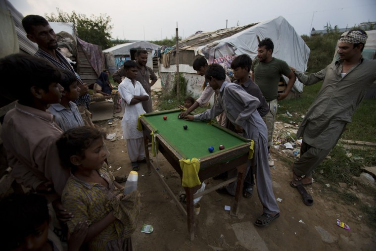 People from a nomad tribe play snooker in their neighborhood in Rawalpindi, Pakistan, Wednesday, Aug. 19, 2015. These nomadic families earn their living collecting recyclable scrap to sell. (AP Photo/B.K. Bangash)