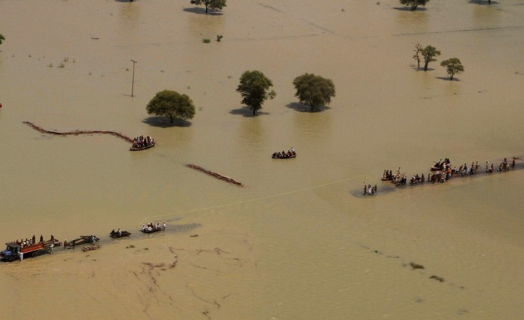 People travel on a road submerged by floodwater in Rajanpur, Pakistan, Thursday, Aug. 6, 2015. Torrential rains and flash floods have hit various villages and cities across the country, forcing the authorities to declare an emergency and issue alerts. The National Disaster Management Authority said the floods, which began in early July, have affected 900,000 people in 2,495 villages across Pakistan. (AP Photo/Asim Tanveer)