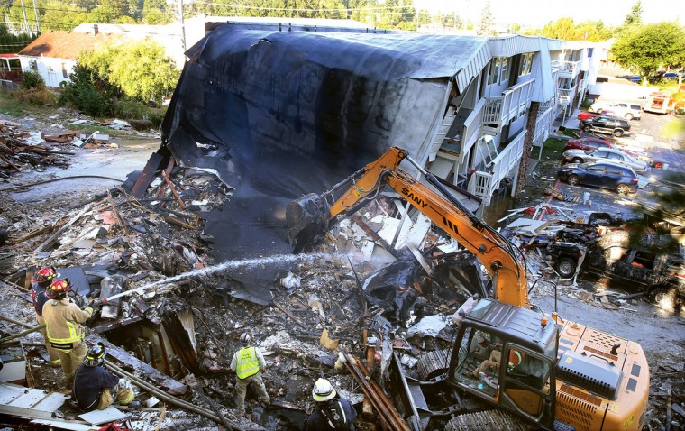 Firefighters hose down the debris field from the collapsed east side of the Bremerton Motel 6, Wednesday morning, Aug. 19, 2015. A gas explosion leveled the building Tuesday evening. The blast critically injured a gas company worker minutes after the acting hotel manager had evacuated the building due to a gas leak. (Larry Steagall/Kitsap Sun via AP)