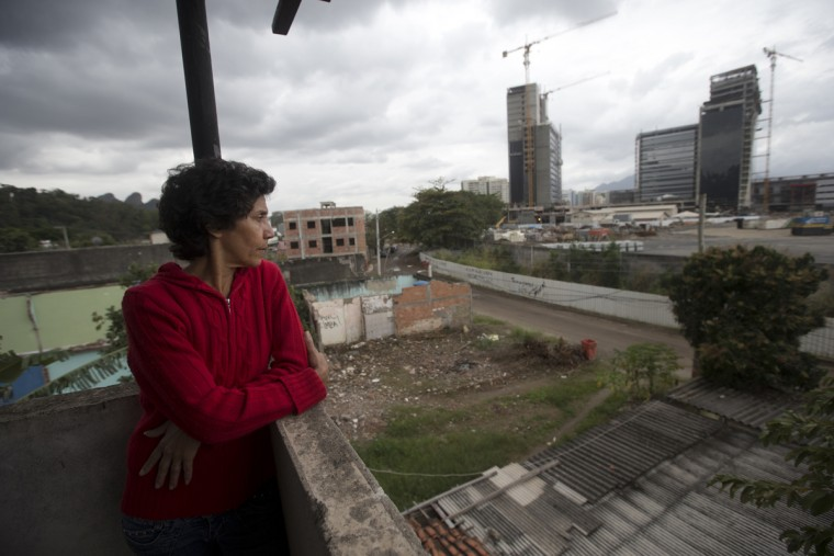 In this July 23, 2015 photo, Marina da Penha, who doesn't want to leave her house, looks the Olympic Park construction site from her home, at the Vila Autodromo slum, in Rio de Janeiro, Brazil. A large section of the Olympic Park will be developed as residential space. Some of that space has yet to be vacated with residents of Vila Autodromo holding out for better compensation from the city. (AP Photo/Silvia Izquierdo)