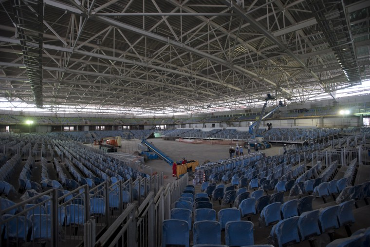 In this July 22, 2015 photo, personnel work at the Carioca Arena 1, that will host basketball during the 2016 Olympic games, in Rio de Janeiro, Brazil. The Olympics offer 28 sports, 300 events, 10,500 athletes and, with the exception of five football venues, it's all packed into Rio for 17 days. The Paralympics add two more weeks, and thousands more athletes. (AP Photo/Silvia Izquierdo)