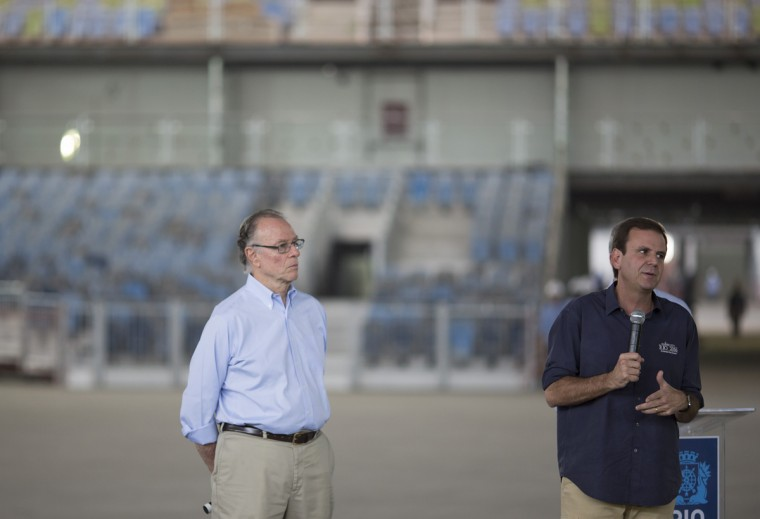 Rio de Janeiro's Mayor Eduardo Paes speaks to the press as Brazil's Olympic Committee President Carlos Nuzman looks on inside a stadium under construction, one year before the Olympic games start, at Olympic Park in Rio de Janeiro, Brazil, Wednesday, Aug. 5, 2015. (AP Photo/Leo Correa)