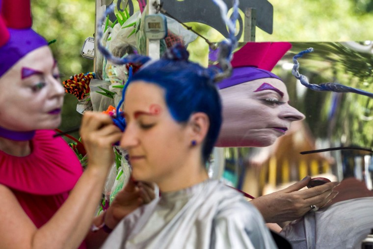 A Spanish hairdresser works in the theatre and dance tent, during the 23rd Sziget (Island) Festival in Northern Budapest, Hungary, Wednesday, Aug. 12, 2015. The Sziget Festival is a five-day annual music and arts event attractig top music artists. (Zsolt Szigetvary/MTI via AP)