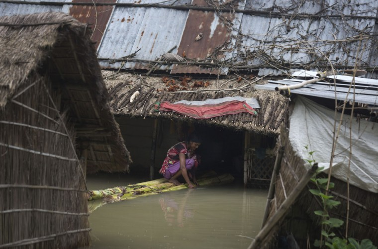 Seated on a makeshift bamboo craft, an Indian woman cleans utensils next her partially flooded house in Murkata village, about 60 kilometers (37 miles) east of Gauhati, India, Sunday, Aug. 23, 2015. The flooding in India's northeastern Assam state is the worst in the past three years, affecting nearly 600,000 people in 19 of the state's 27 districts, officials said. (AP Photo/Anupam Nath)