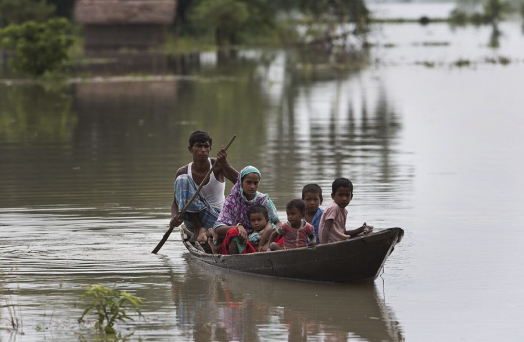 A flood affected family travel on a boat to a safer area in Murkata village, about 60 kilometers (37 miles) east of Gauhati, India, Sunday, Aug. 23, 2015. The flooding in India's northeastern Assam state is the worst in the past three years, affecting nearly 600,000 people in 19 of the state's 27 districts, officials said. (AP Photo/Anupam Nath)