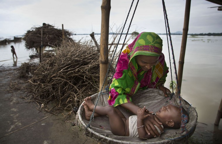 An Indian woman consoles her baby in the flood affected village of Morisuti, about 65 kilometers (40 miles) east of Gauhati, India, Sunday, Aug. 23, 2015. The flooding in India's northeastern Assam state is the worst in the past three years, affecting nearly 600,000 people in 19 of the state's 27 districts, officials said. (AP Photo/Anupam Nath)