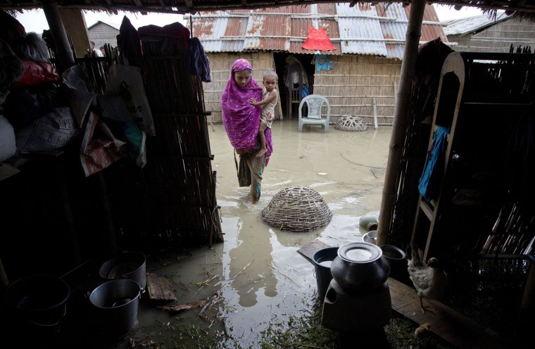An Indian family walks inside house partially flooded due monsoon rains in Xandohkhaitee village, about 80 kilometers (50 miles) east of Gauhati, India , Saturday, Aug. 22, 2015. State authorities say that monsoon flooding has nearly 200,000 people to leave their homes and take shelter in state-run tents this week. The area is prone to flooding during the June-to-September monsoon season. (AP Photo/Anupam Nath)