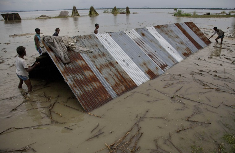 Villagers try to repair a house damaged during monsoon floods in Xandohkhaitee village, about 80 kilometers (50 miles) east of Gauhati, India , Saturday, Aug. 22, 2015. State authorities say that monsoon flooding has nearly 200,000 people to leave their homes and take shelter in state-run tents this week. The area is prone to flooding during the June-to-September monsoon season. (AP Photo/Anupam Nath)