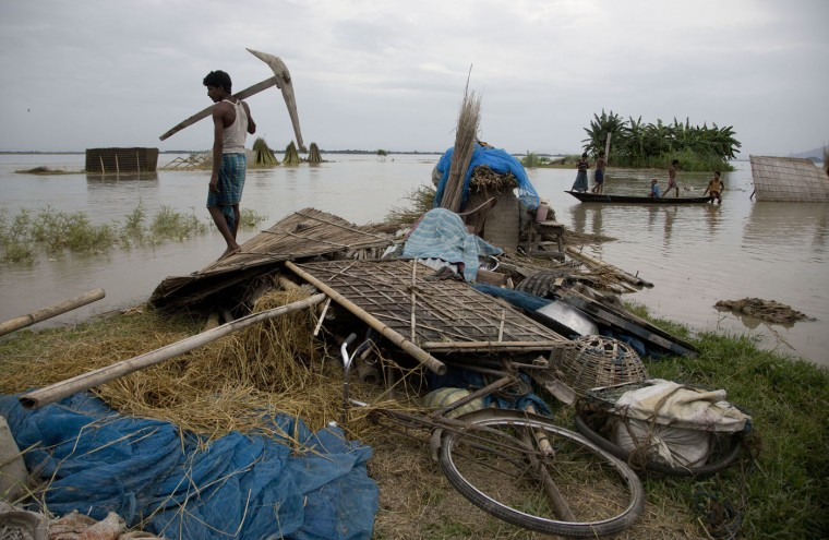 An Indian man gathers belongings from a flood affected area in Xandohkhaitee village, about 80 kilometers (50 miles) east of Gauhati, India , Saturday, Aug. 22, 2015. State authorities say that monsoon flooding has nearly 200,000 people to leave their homes and take shelter in state-run tents this week. The area is prone to flooding during the June-to-September monsoon season. (AP Photo/Anupam Nath)