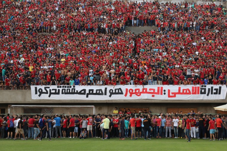 """Ultras Ahlawy, the hardcore fan base of Al-Ahly football club, watch players train at the Al - Ahly club in Cairo, Egypt. Ultras, whose name comes from the Latin word for ìbeyond,î started in Latin America and Europe in the 1950s and eventually made it to Arab countries, with particularly strong followings in North Africa. The first to form in Egypt, Ultras White Knights, emerged in 2007 to support the Zamalek team. Groups backing arch-rival al-Ahly and others soon followed. Arabic on the banner reads, """"the Al-Ahly administration: the fans are the most important group to be moved."""" (AP Photo/Mohammed El Raai)"""