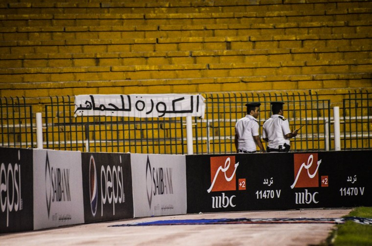 """Security forces walk during a match between Zamalek and ENPPI at the Arab Contractors Stadium, in Cairo. Egyptian authorities have banned fans from attending football games, citing ongoing tension between security forces and Ultras hardcore soccer fan groups since a 2012 stadium disaster in Port Said in which at least 72 football fans were killed. Arabic on the banner reads, """"soccer is for fans."""" (AP Photo/Mohammed El Raai)"""