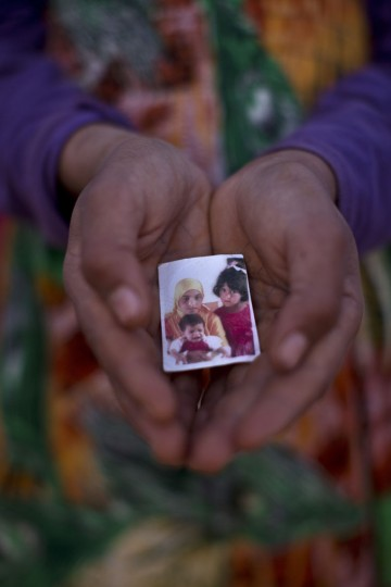 In this Wednesday, July 22, 2015 photo, Syrian refugee Hannan Mohammed, 12, holds a picture of herself and her sister Warda, 5, and the youngest Jawahir, 1, who died last February after suffering from chronic malnutrition, outside their tent at an informal tented settlement near the Syrian border on the outskirts of Mafraq, Jordan. Of the 4 million refugees who fled Syriaís grinding civil war, it is the conflictís youngest exiles, like Jawahir, who often bear the brunt of its woes. (AP Photo/Muhammed Muheisen)
