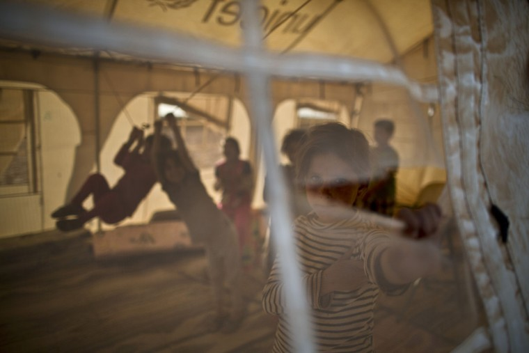 In this Wednesday, July 22, 2015 photo, a Syrian refugee girl looks through the hole of a makeshift school at an informal tented settlement near the Syrian border on the outskirts of Mafraq, Jordan. More than 10,000 children have died in Syria's four-year conflict, while over 2.8 million in and out of the country donít go to school, according to the U.N. children's agency, UNICEF. (AP Photo/Muhammed Muheisen)