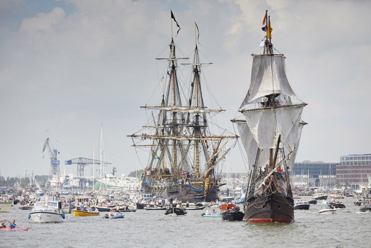 Tall ships escorted by small boats arrive in Amsterdam, Netherlands, Wednesday, Aug. 19, 2015, to participate in SAIL Amsterdam 2015, a five-yearly festival celebrating the Dutch capital's maritime history that is expected to draw some 2 million visitors. The 9th edition of the nautical event lasts until Sunday, Aug. 23 on and around the IJ river. (AP Photo/Phil Nijhuis)