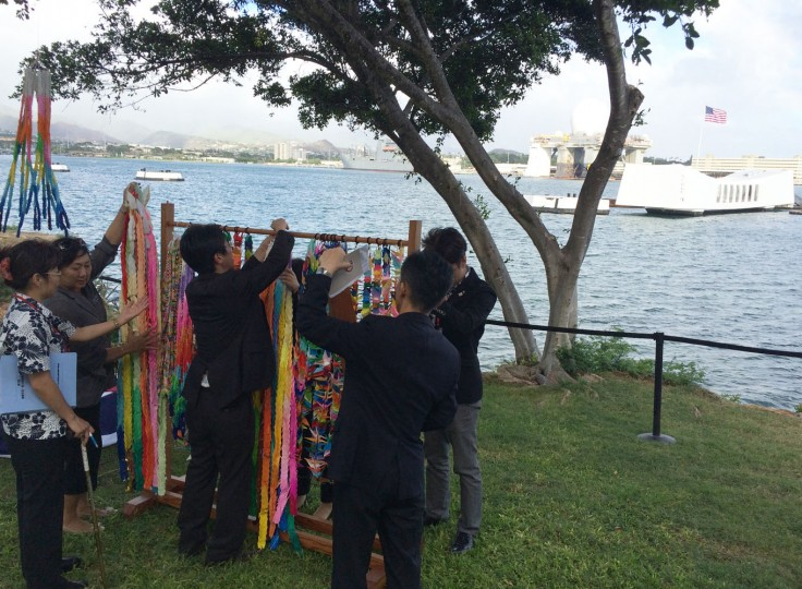 People hang paper cranes folded for peace near a memorial to the sunken battleship USS Arizona before a ceremony marking the 70th anniversary of the end of World War II, Friday, Aug. 14, 2015, in Pearl Harbor, Hawaii. Mayors and city council members from Honolulu and Nagaoka, Japan, joined the U.S. Pacific Fleet commander to lay wreaths and unveil a new plaque. (AP Photo/Audrey McAvoy)
