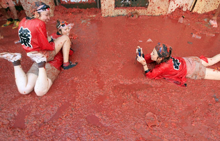 "Two woman have their photo taken as they pose in a puddle of squashed tomatoes during the annual ""tomatina"" tomato fight fiesta, in the village of Bunol, 50 kilometers outside Valencia, Spain, Wednesday, Aug. 26, 2015. The streets of an eastern Spanish town are awash with red pulp as thousands of people pelt each other with tomatoes in the annual ""Tomatina"" battle that has become a major tourist attraction. At the annual fiesta in Bunol on Wednesday, trucks dumped 150 tons of ripe tomatoes for some 22,000 participants, many from abroad to throw during the hour-long morning festivities. (AP Photo/Alberto Saiz)"