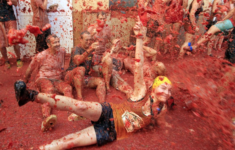 "People sit and lie on the ground during the annual ""tomatina"" tomato fight fiesta, in the village of Bunol, 50 kilometers outside Valencia, Spain, Wednesday, Aug. 26, 2015. The streets of an eastern Spanish town are awash with red pulp as thousands of people pelt each other with tomatoes in the annual ""Tomatina"" battle that has become a major tourist attraction. At the annual fiesta in Bunol on Wednesday, trucks dumped 150 tons of ripe tomatoes for some 22,000 participants, many from abroad to throw during the hour-long morning festivities. (AP Photo/Alberto Saiz)"