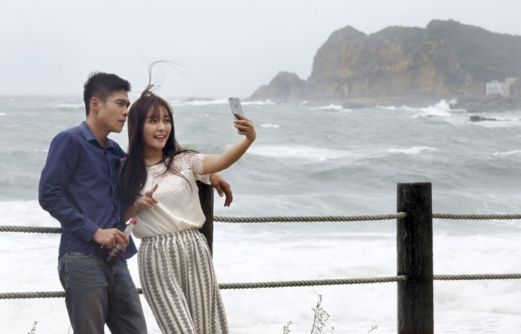 "A couple takes a ""selfie"" photograph in front of the crashing waves from Typhoon Soudelor off the coast of Keelung, northeastern Taiwan, Friday, Aug. 7, 2015. Soudelor is expected to bring heavy rains and strong winds to the island late Friday with winds speeds over 170 km per hour (100 mph) and gusts over 200 km per hour (120 mph) according to Taiwan's Central Weather Bureau. (AP Photo/Wally Santana)"