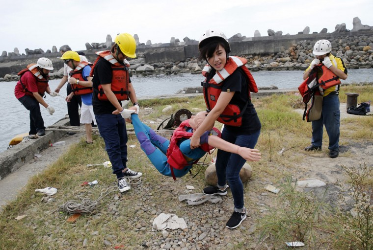 "Employees of commercial ships and fishing vessels ""rescue"" a dummy during an emergency rescue drill as Typhoon Soudelor approaches in Keelung, northeastern Taiwan, Friday, Aug. 7, 2015. Soudelor is expected to bring heavy rains and strong winds to the island late Friday with winds speeds over 170 km per hour (100 mph) and gusts over 200 km per hour (120 mph) according to Taiwan's Central Weather Bureau. (AP Photo/Wally Santana)"