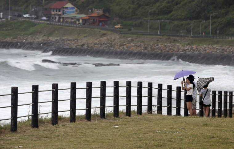 Visitors to a coastal park photograph waves from approaching Typhoon Soudelor in Keelung, northeastern Taiwan, Friday, Aug. 7, 2015. Soudelor is expected to bring heavy rains and strong winds to the island late Friday with winds speeds over 170 km per hour (100 mph) and gusts over 200 km per hour (120 mph) according to Taiwan's Central Weather Bureau. (AP Photo/Wally Santana)