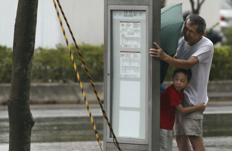 A man and a boy shelter behind a bus stop in the strong winds from Typhoon Soudelor in Taipei, Taiwan, Friday, Aug. 7, 2015. Soudelor is expected to bring heavy rains and strong winds to the island late Friday with winds speeds over 170 km per hour (100 mph) and gusts over 200 km per hour (120 mph) according to Taiwan's Central Weather Bureau. (AP Photo/Wally Santana)