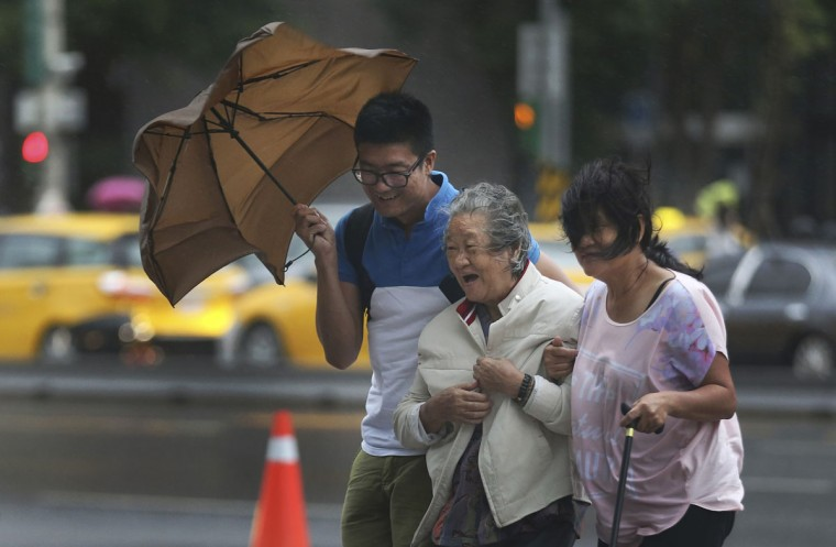 An elderly woman is escorted in the strong winds from Typhoon Soudelor in Taipei, Taiwan, Friday, Aug. 7, 2015. Soudelor is expected to bring heavy rains and strong winds to the island late Friday with winds speeds over 170 km per hour (100 mph) and gusts over 200 km per hour (120 mph) according to Taiwan's Central Weather Bureau. (AP Photo/Wally Santana)