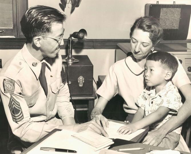 Sgt. Thomas Moy registers his son, Thomas Moy Jr., at school with Mrs. Evelyn Giraridin at Montebello School. (Richard Stacks/Baltimore Sun, 1952)