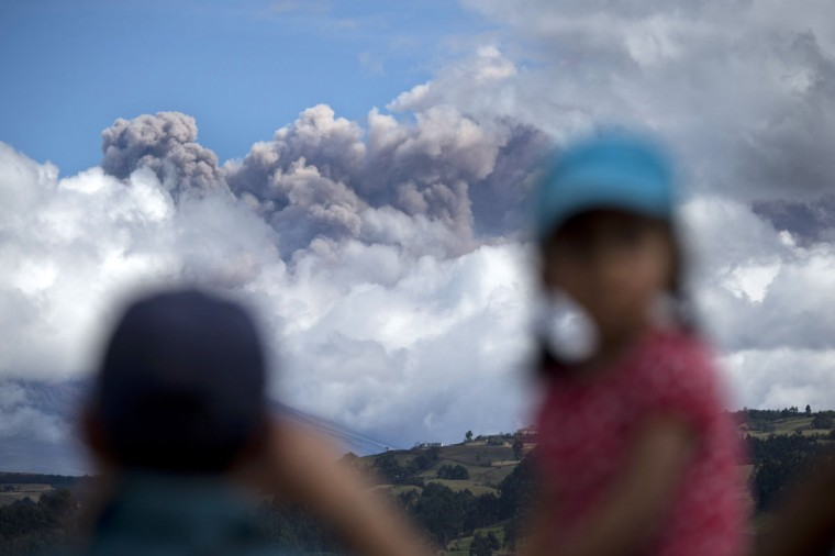Children look at the ashes spewed by the Cotopaxi volcano in Sangolqui, Ecuador on August 23, 2015. A dozen towns of central Ecuador, including Quito sector, suffered Saturday the ashes of the Cotopaxi volcano, which started erupting a week ago after 138 years, as crops and cattle were affected. (MARTIN BERNETTI/AFP/Getty Images)