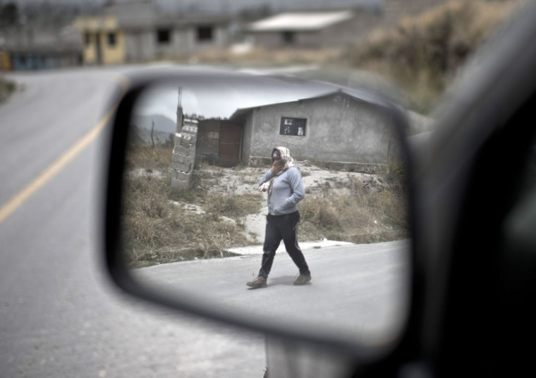 A woman is reflected on a mirror as she walks along a street covered with ashes of the Cotopaxi volcano in Lasso, Ecuador on August 23, 2015. A dozen towns of central Ecuador, including Quito sector, suffered Saturday the ashes of the Cotopaxi volcano, which started erupting a week ago after 138 years, as crops and cattle were affected. (MARTIN BERNETTI/AFP/Getty Images)