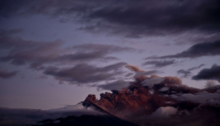 View from Sangolqui of the Cotopaxi volcano in Ecuador spewing ashes on August 23, 2015. Nearly 325,000 people could be affected by an eruption of Cotopaxi, the volcano looming beyond the Ecuadoran capital of Quito, officials said Monday. The biggest risk is from an eruption melting the 5,900-metre (19,000-foot) mountain's snowcap and triggering massive melt-water floods and lahar mudflows that could sweep through nearby towns, Ecuador's minister of risk management Maria del Pilar Cornejo told a press conference. (MARTIN BERNETTI/AFP/Getty Images)