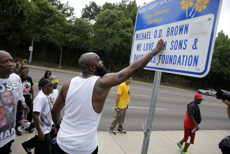 Michael Brown Sr. stops to touch an adopt-a-highway sign as he takes part in a parade in honor of his son, Michael Brown, Saturday, Aug. 8, 2015, in Jennings, Mo. Sunday will mark one year since Michael Brown was shot and killed by Ferguson police officer Darren Wilson. (Jeff Roberson/Associated Press)