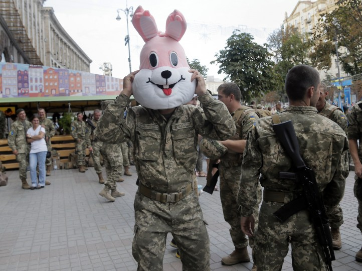 A soldier tries a cartoons character's costume on during a rehearsal for the Independence Day military parade in the center of Kiev, Ukraine, Saturday, Aug. 22, 2015. (Efrem Lukatsky/Associated Press)