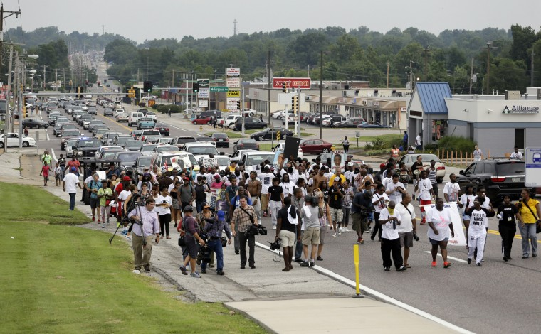 People march down West Florissant Avenue during a parade in honor of Michael Brown Saturday, Aug. 8, 2015, in Jennings, Mo. Sunday will mark one year since Michael Brown was shot and killed by Ferguson police officer Darren Wilson. (Jeff Roberson/Associated Press)