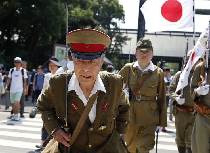 Japanese men clad in outdated military costumes march o pay respects to the country's war dead at the Yasukuni Shrine in Tokyo, Saturday, Aug. 15, 2015. Japan marked the 70th anniversary of the end of World War II. (Shuji Kajiyama/Associated Press)