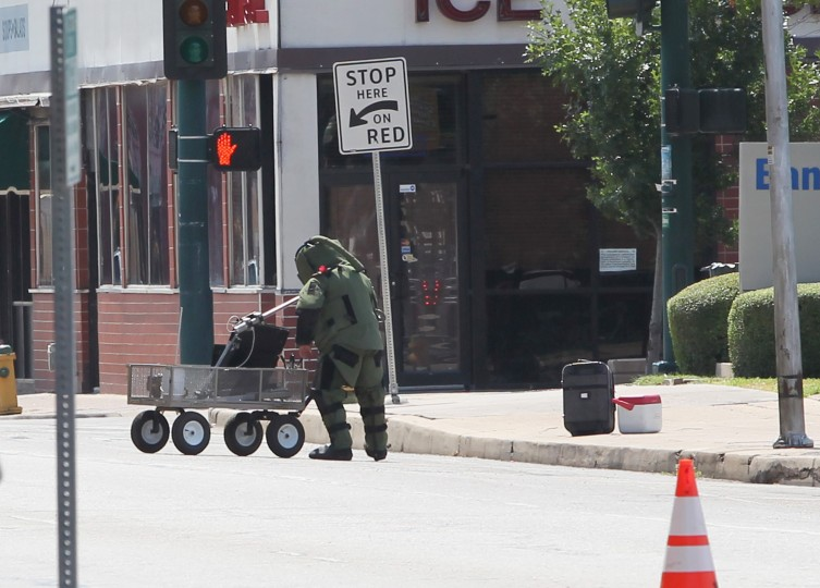 A McLennan county bomb expert pulls out equipment while standing next to a unidentified ice chest and luggage, Saturday, Aug. 22, 2015, in Waco, Texas. Law enforcement officers cleared portions of downtown Waco during a biker rally in protest of the handling of the Twin Peaks restaurant shooting. Nine people were killed and twice as many injured in what authorities say was an apparent confrontation May 17 between two rival motorcycle gangs. The robot found no hazardous materials. (Jerry Larson/Waco Tribune-Herald via AP)